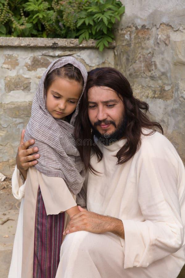 Gesù che conforta una bambina fotografie stock