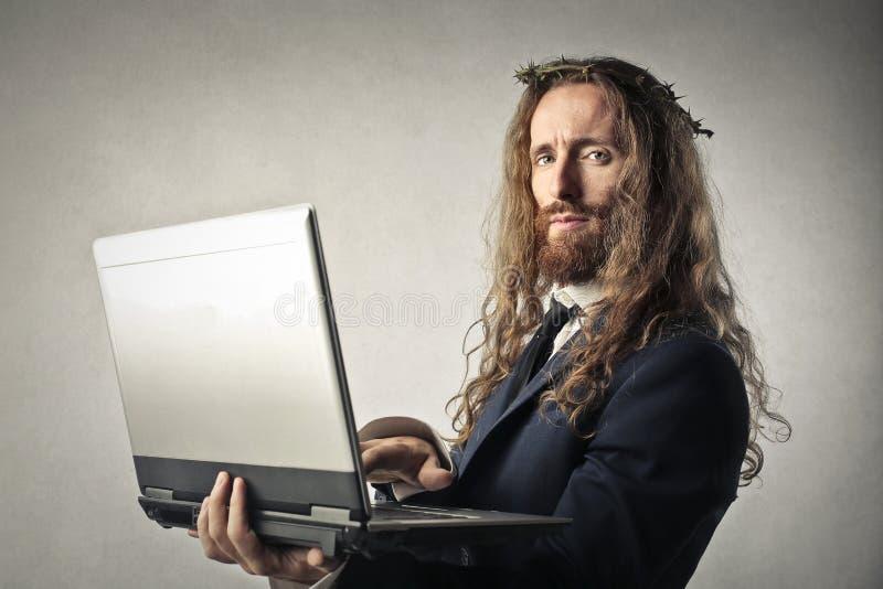 Gesù che controlla il suo computer portatile immagine stock