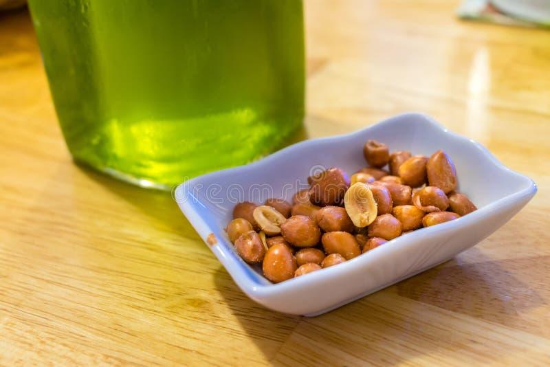Gesalzene gebratene Erdnüsse in einer Platte nahe grünem Bier auf einer Tabelle lizenzfreies stockbild
