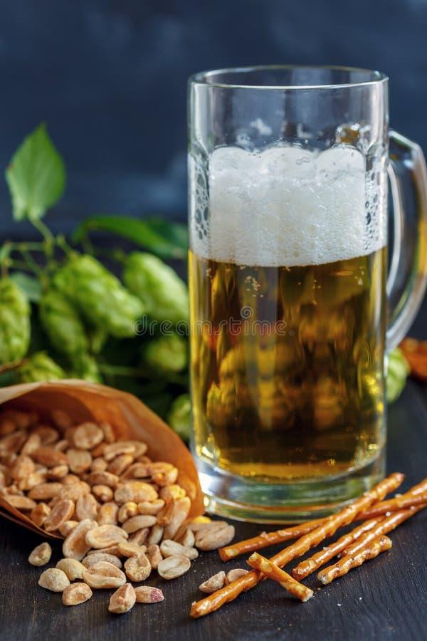 Gesalzene Stöcke, Erdnüsse und Becher Bier stockbild