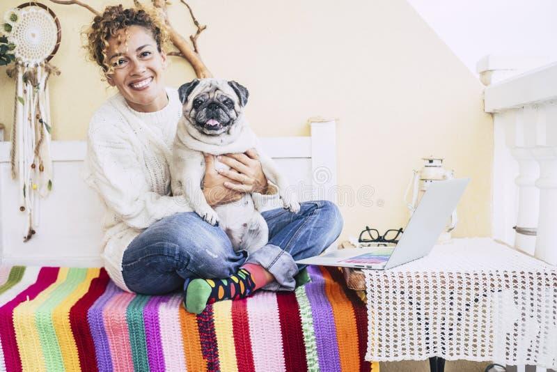 Gesamtglück für die schöne nette kaukasische junge Frau umarmte mit ihrem fetten Pug Hund der besten Freunde auch lächelnd Freund lizenzfreie stockfotografie