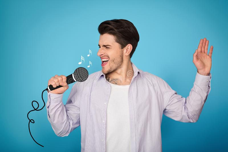 Gesang des jungen Mannes laut gegen blauen Hintergrund lizenzfreie stockfotografie
