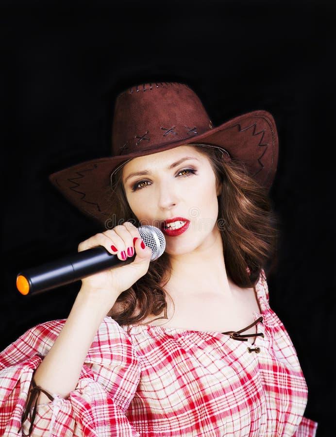 Gesangcowgirl des schönen Brunette im Cowboyhut auf dunklem Hintergrund lizenzfreies stockfoto