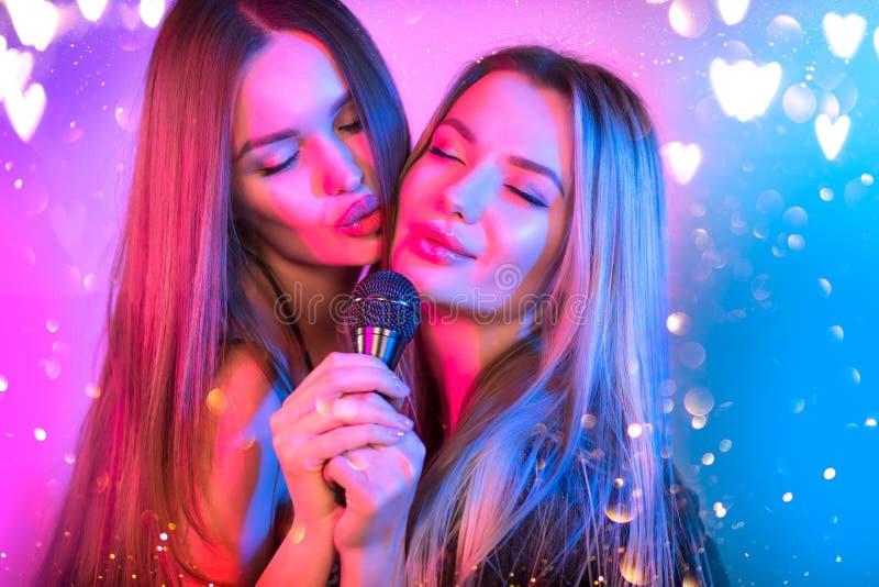 Gesangsende Frauen mit Mikrofon, Party, Karaoke Bar Beauty Glamour Girl-Freunde Singen und Tanzen auf Stage Rock Sänger lizenzfreie stockfotografie