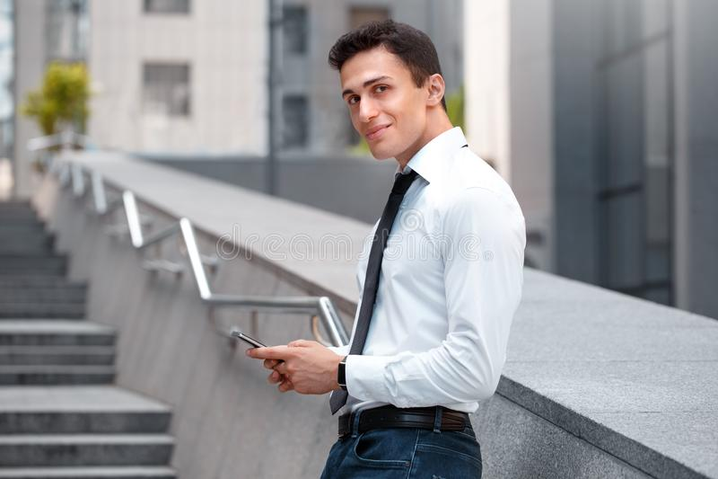 Geschäfts-Lebensstil Geschäftsmann, der auf Wand auf der Stadtstraße mit dem Smartphone schaut die Kamera neugierig sich lehnt lizenzfreie stockfotografie