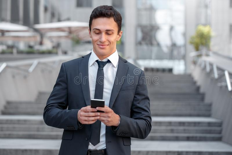 Geschäfts-Lebensstil Geschäftsmannstellung auf der Stadtstraße, die Medien auf dem Smartphone froh überprüft stockfotos