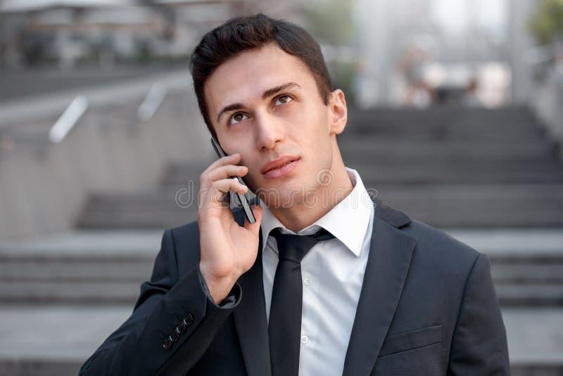 Geschäfts-Lebensstil Geschäftsmannstellung auf der Stadtstraße, die auf nachdenklicher Nahaufnahme des Smartphone spricht stockbild