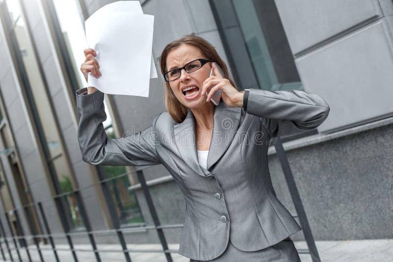 Geschäftsfrau in den Brillen, die auf der Stadtstraße mit Dokumenten herauf die Argumentierung auf dem Smartphone emotional stehe lizenzfreie stockfotografie