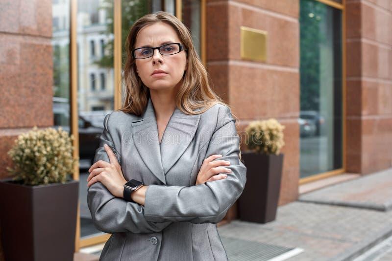 Geschäftsfrau in den Brillen, die auf der Stadtstraße stehen, kreuzte die unverschämten Arme stockbild