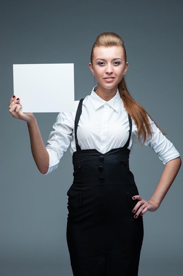Geschäftsfrau mit leerer Werbungsfahne auf Weiß stockfoto