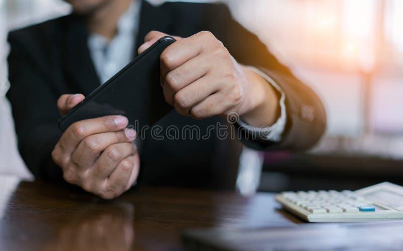 Geschäftsmann, der Spiel und online genießen, Hände halten Smartphone spielt stockfotos