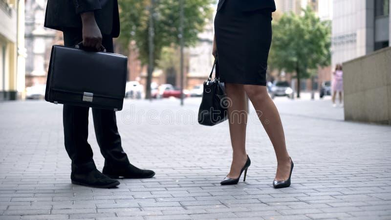 Geschäftsmann und Frau, die auf Straße, modernen klassischen Schuhen und Aktenkoffer sprechen lizenzfreie stockfotos