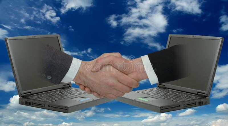 Geschäftsmannhändedruck Zwei männliche Hände, die von den Laptops auftauchen lizenzfreies stockbild