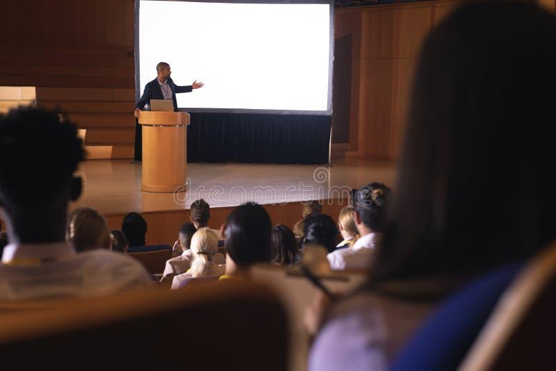 Geschäftsmannstellung nahe Podium und geben Darstellung auf weißem Projektor im Auditorium lizenzfreie stockfotos