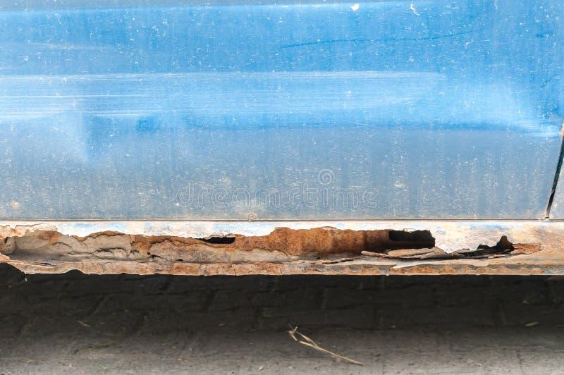 Geschädigter blauer Autometallkörper und verkratzte Farbe mit rostigen korrodierten Teilen und Loch auf der Unterseite bereit zur stockfoto