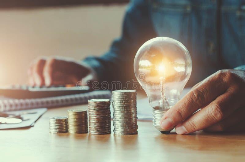 Geschäft accountin mit Einsparungsgeld mit der Hand, die Glühlampe hält stockfotografie