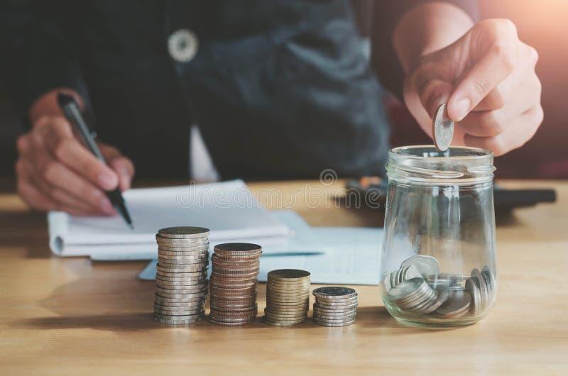 Geschäft accountin mit Einsparungsgeld mit der Hand, die herein Münzen setzt lizenzfreies stockfoto
