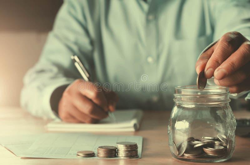 Geschäft accountin mit Einsparungsgeld mit der Hand, die herein Münzen setzt lizenzfreies stockbild
