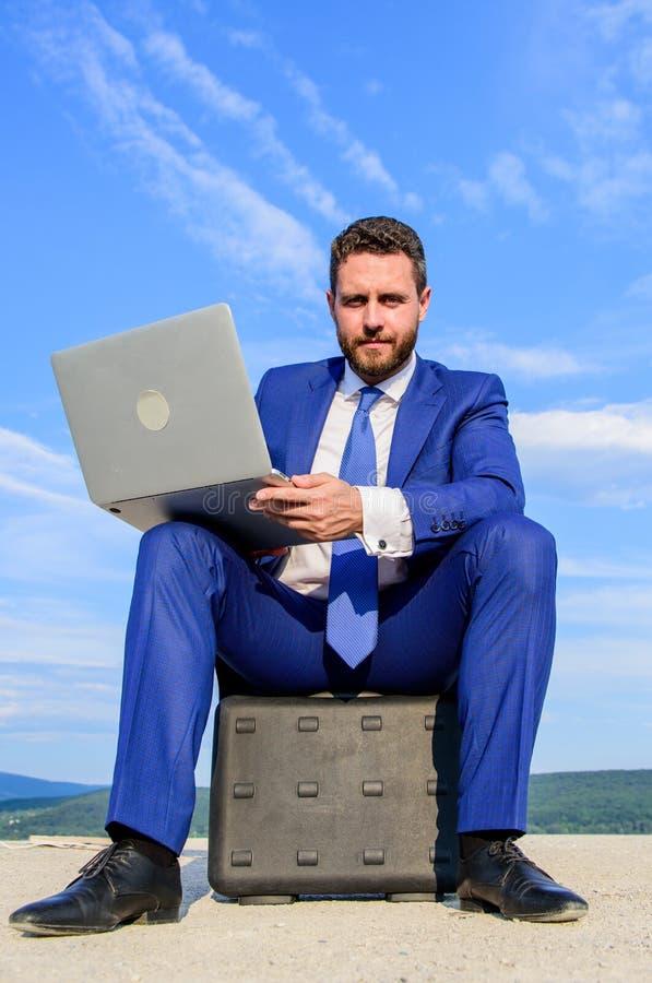 Geschäft auf Frischluft Geschäftsmann mit Laptop sitzen Hintergrund des blauen Himmels des Aktenkoffers Unentbehrliches Attribut  stockbilder