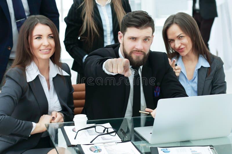 Geschäft: Berufsgeschäftsteam nahe dem Arbeitsplatz mit Ihren Fingern vorwärts zeigend stockfoto