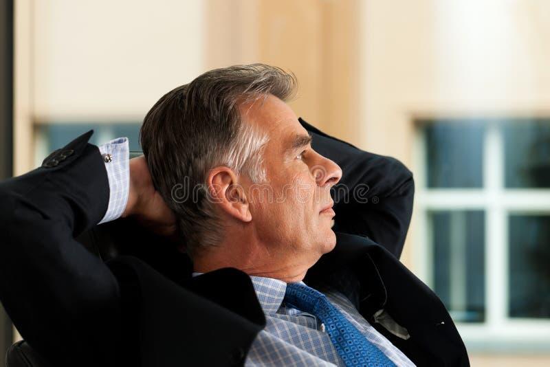Geschäft - Chef, der in seinem Büro erwägt stockfotografie
