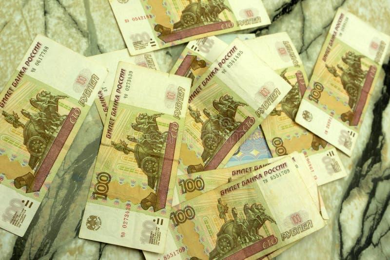 Geschäft, Finanzierung, Einsparung, Bankwesen und Leutekonzept - nahes hohes Bündel Geld russische Banknoten hundert Rubel lizenzfreie stockfotografie
