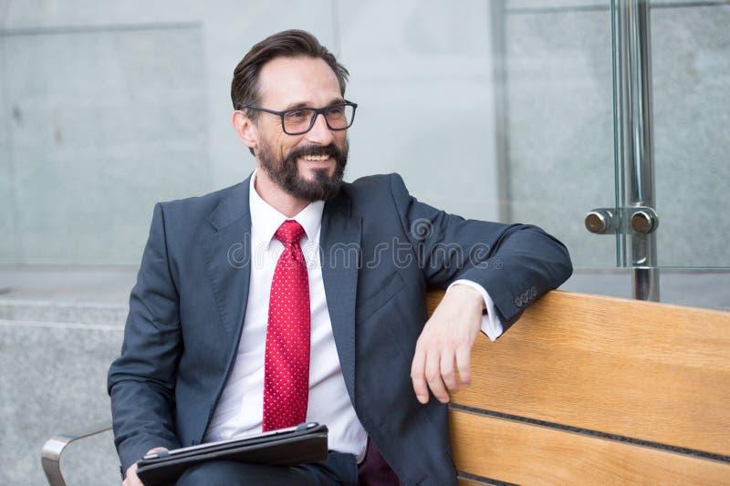Geschäft, Freizeit, Technologie, Kommunikation und Leutekonzeptmann mit Tablette auf Stadtstraße setzen auf die Bank Portrait des lizenzfreies stockfoto