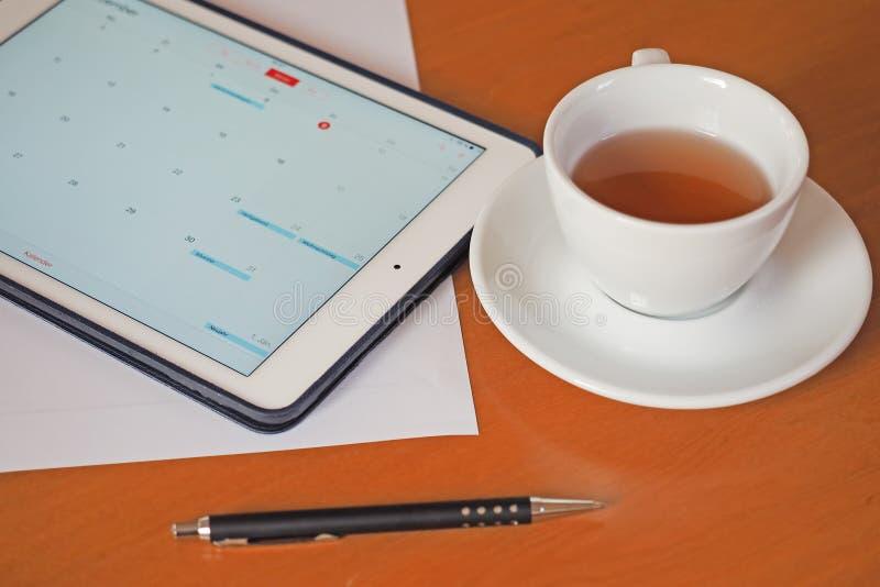 Geschäft, Kalender, Verabredung Bürotisch mit Notizblock, Computer, Kaffeetasse stockbild