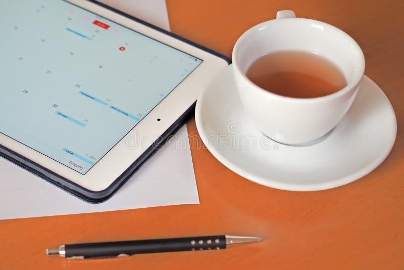 Geschäft, Kalender, Verabredung Bürotisch mit Notizblock, Computer, Kaffeetasse stockfotos