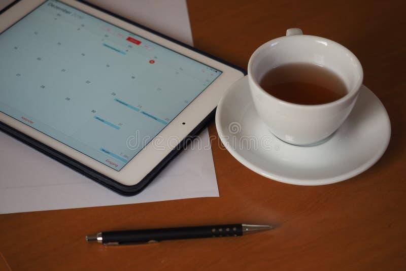 Geschäft, Kalender, Verabredung Bürotisch mit Notizblock, Computer, Kaffeetasse stockfotografie