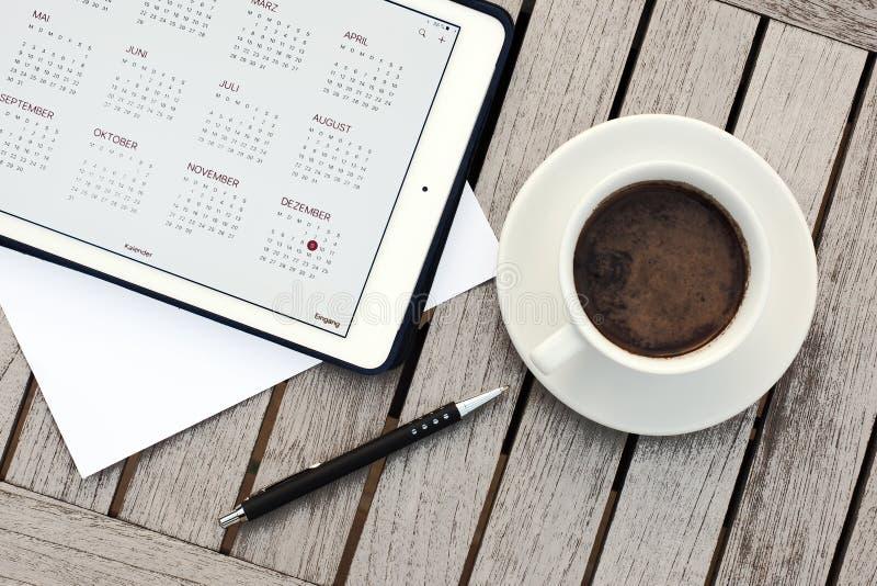 Geschäft, Kalender, Verabredung Bürotisch mit Notizblock, Computer, Kaffeetasse lizenzfreies stockbild