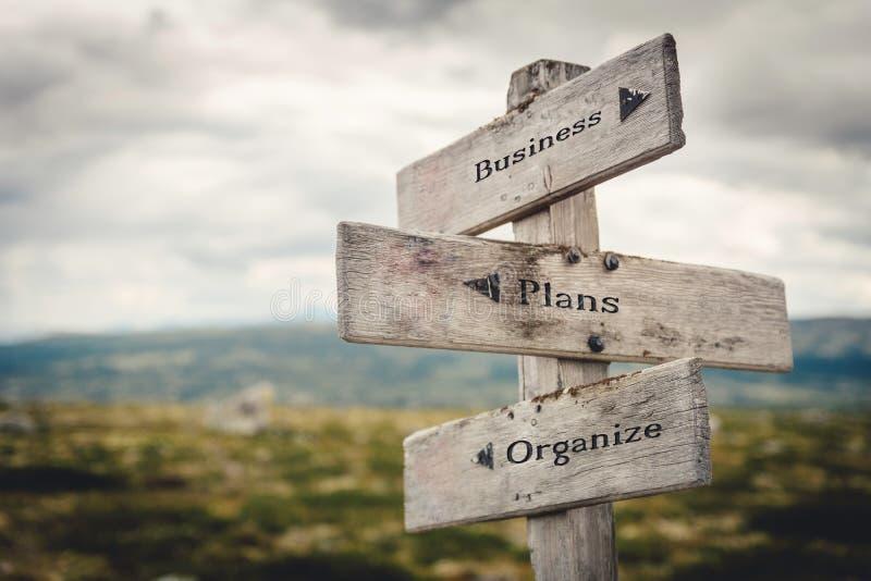 Geschäft, Pläne und hölzernes Wegweiserfreien in der Natur organisieren stockbilder