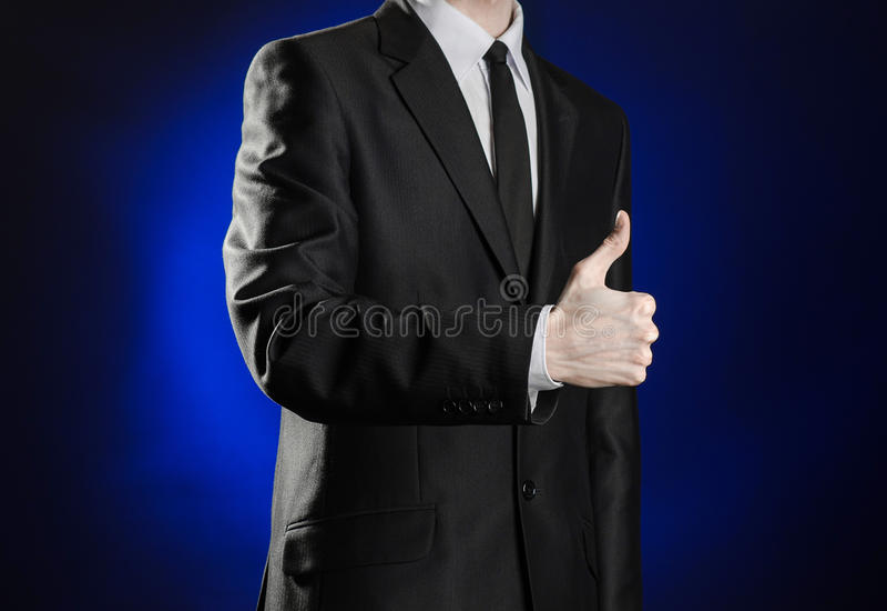 Geschäft und die Darstellung des Themas: bemannen Sie in einem schwarzen Anzug, der Handzeichen auf einem dunkelblauen Hintergrun lizenzfreies stockbild