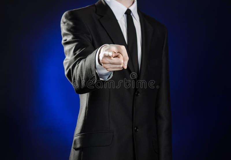 Geschäft und die Darstellung des Themas: bemannen Sie in einem schwarzen Anzug, der Handzeichen auf einem dunkelblauen Hintergrun lizenzfreies stockfoto