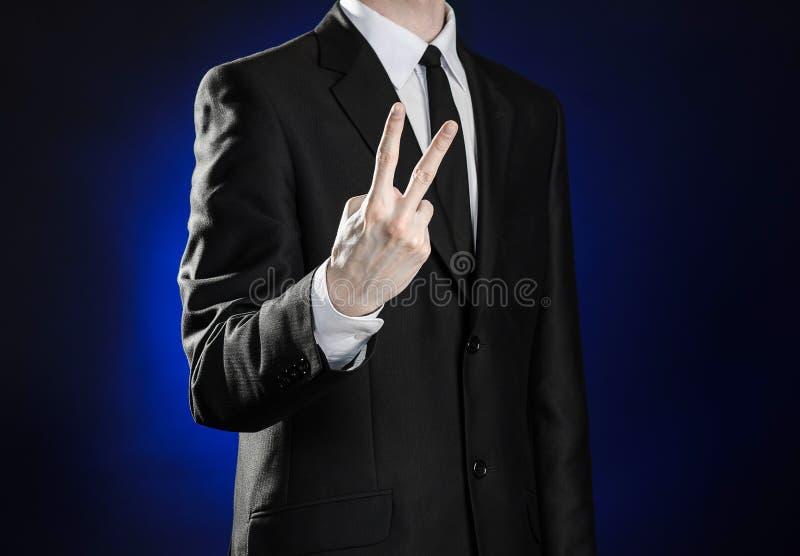 Geschäft und die Darstellung des Themas: bemannen Sie in einem schwarzen Anzug, der Handzeichen auf einem dunkelblauen Hintergrun stockfoto