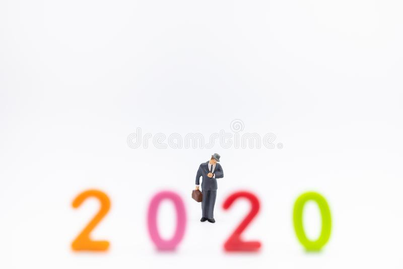 Geschäft und 2020 neues Jahr, die Concpet planen Geschäftsmannminiaturzahl Leute mit dem suitcace, das zur Armbanduhr steht und s lizenzfreie stockfotos