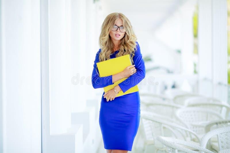 Geschäfts-Dame mit einem gelben Ordner und einem Telefon stockfotos