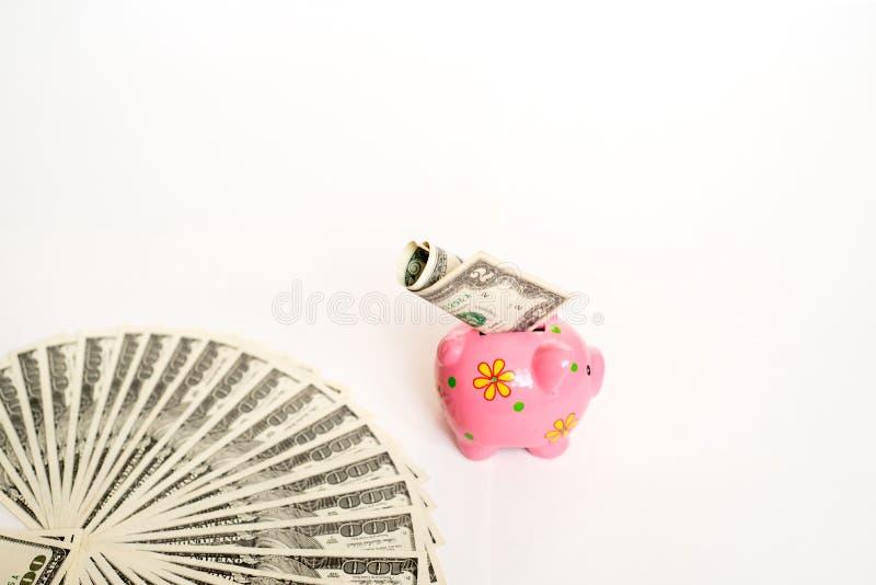 Geschäfts-, Finanz-, Investitions-, Einsparungs- und Korruptionskonzept - nah oben vom Dollarbargeld und -Sparschwein auf Tabelle lizenzfreies stockfoto