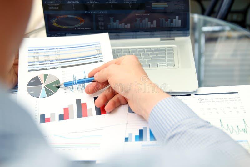 Geschäfts-Geschäftsmann, der Finanzzahlen auf ein den Kollegen der Diagramme s bearbeiten und analysieren Finanzzahlen auf a bear stockfotos