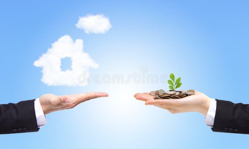 Geschäfts-Hände mit Geld und Haus stockfoto