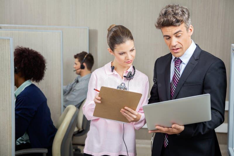 Geschäfts-Kollegen, die in Call-Center sich besprechen lizenzfreie stockbilder