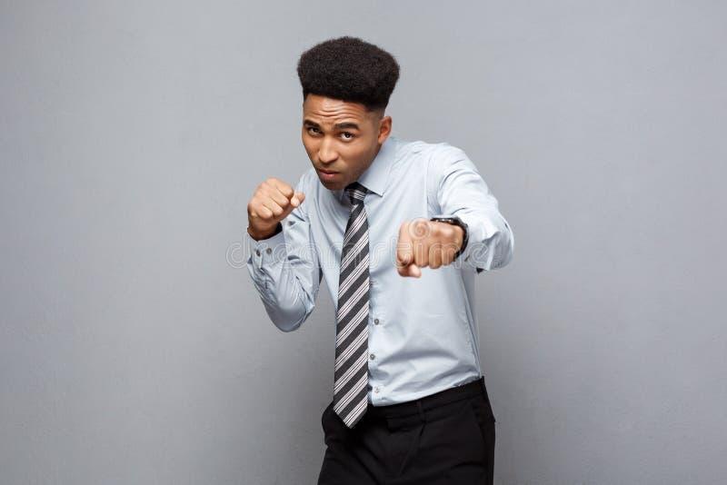 Geschäfts-Konzept - überzeugter netter junger Afroamerikaner in Verpacken poseture über grauem Hintergrund stockfotos