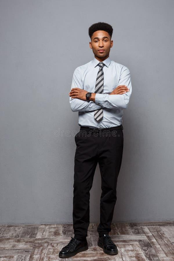 Geschäfts-Konzept - Ganzaufnahme des überzeugten Afroamerikanergeschäftsmannes im Büro stockfoto