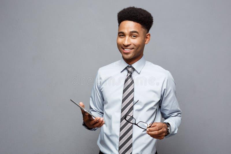 Geschäfts-Konzept - glücklicher hübscher Berufsafroamerikanergeschäftsmann, der digitale Tablette und Gespräch mit Kunden hält stockfoto