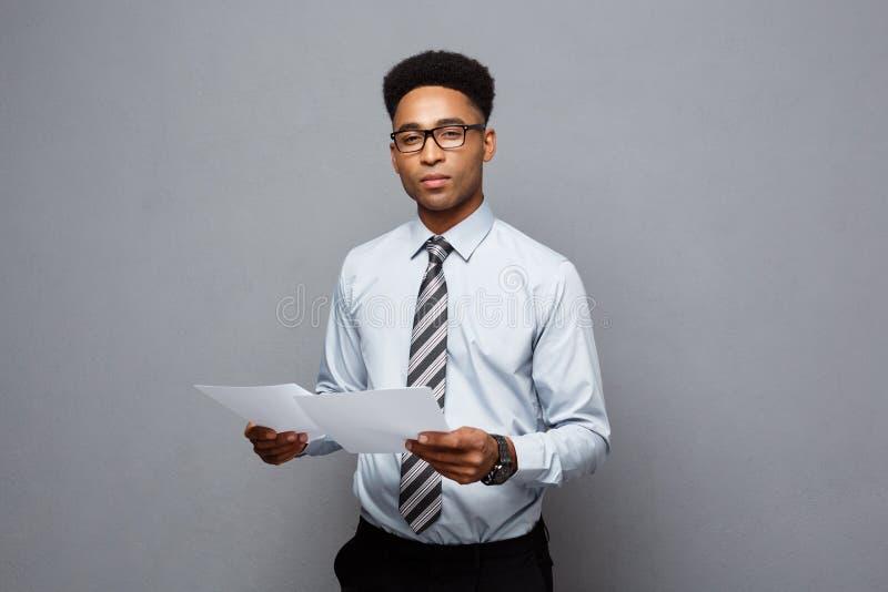 Geschäfts-Konzept - hübscher junger Berufsafroamerikanergeschäftsmann, der Berichtspapiere hält stockfotos