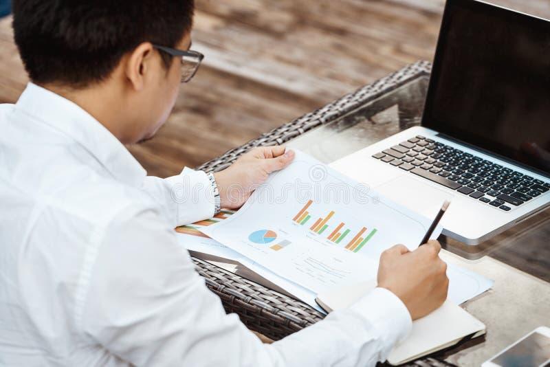 Geschäfts-Konzept - junger Geschäftsmann, der auf Finanzplan woking ist lizenzfreie stockfotos