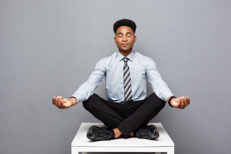 Geschäfts-Konzept - Porträt des Afroamerikanergeschäftsmannes Meditation und Yoga tuend, herein bevor dem Arbeiten lizenzfreie stockbilder