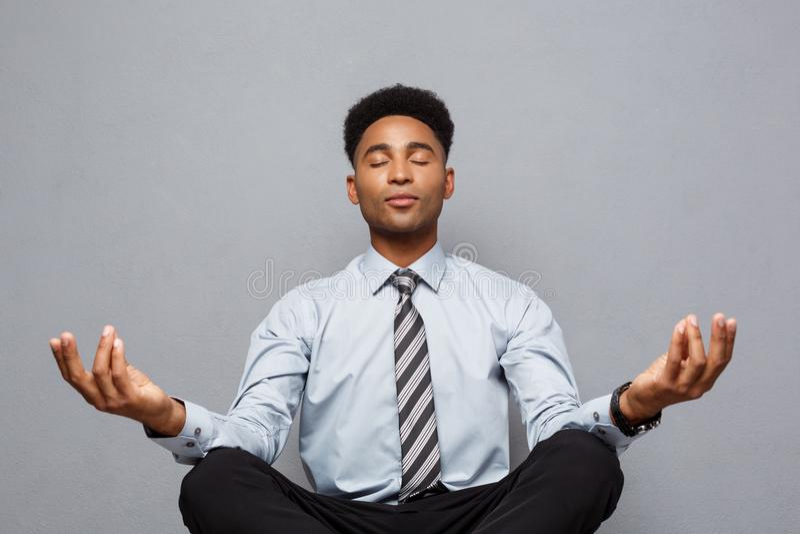Geschäfts-Konzept - Porträt des Afroamerikanergeschäftsmannes Meditation und Yoga tuend, herein bevor dem Arbeiten lizenzfreie stockfotografie
