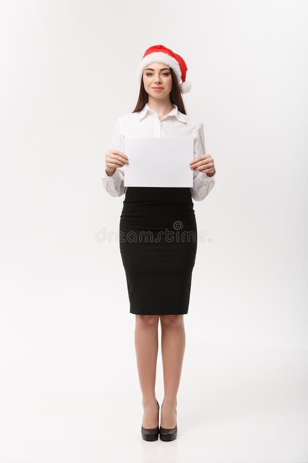 Geschäfts-Konzept - schöne junge überzeugte Geschäftsfrau mit Sankt-Hut, der weißes leeres Papier hält, feiern für stockbild