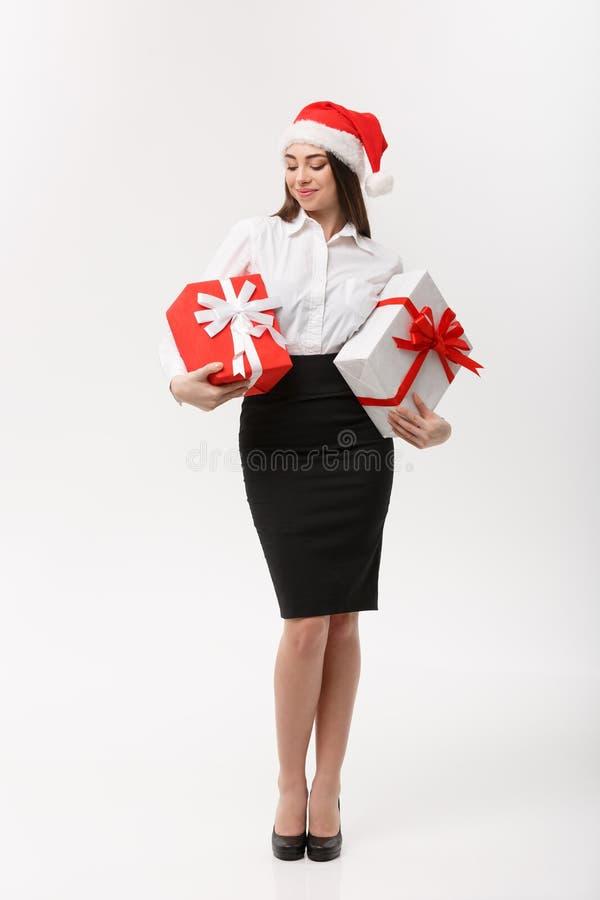 Geschäfts-Konzept - schöne junge kaukasische Geschäftsfrau mit Sankt-Hut, der Geschenkboxen mit Kopienraum auf Seite hält stockbilder